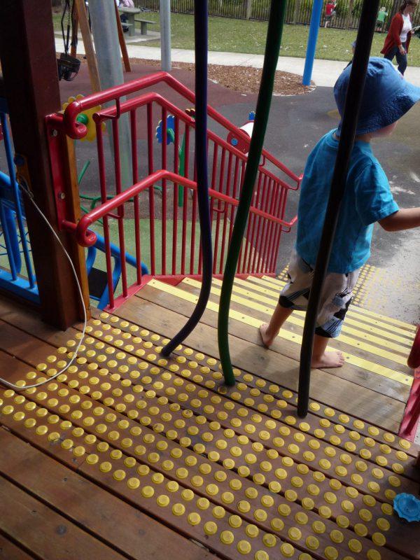 写真:コテージ側から見下ろした階段。入口には、天井から床まで届く太めのホースのような物が3本吊られている。その向こうには階段を下りようとする男の子