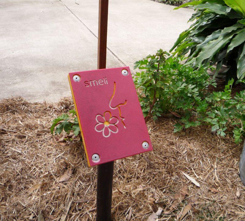 写真:ハーブガーデンに設置された小さなパネル。Smellの文字と、花の匂いをかぐ人の横顔の絵。どちらも触って分かるように彫り込まれている