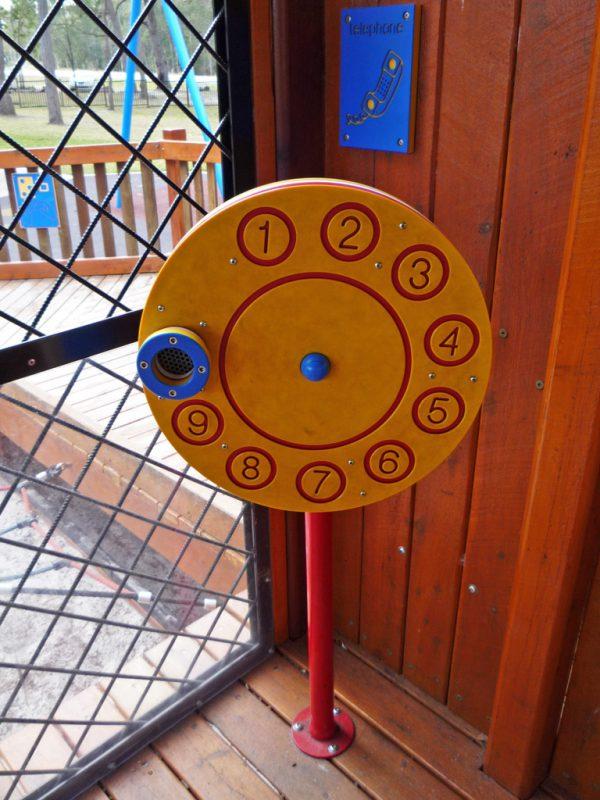 写真:デッキの隅にある電話コーナー。鉄製の支柱の先に直径60センチほどの円盤が床に対して垂直に設置されている。円盤には電話のダイヤルの模様が彫り込まれている