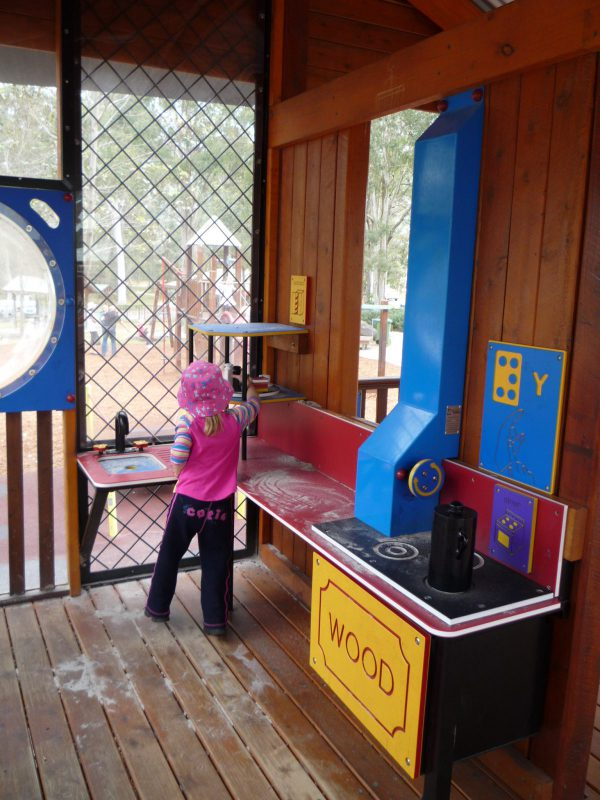 写真:コテージのキッチンコーナー。オーブンや、車いすもアクセスしやすいカウンターなどがある。シンクのそばに立つ女の子がカップボードに手を伸ばしてままごとの最中