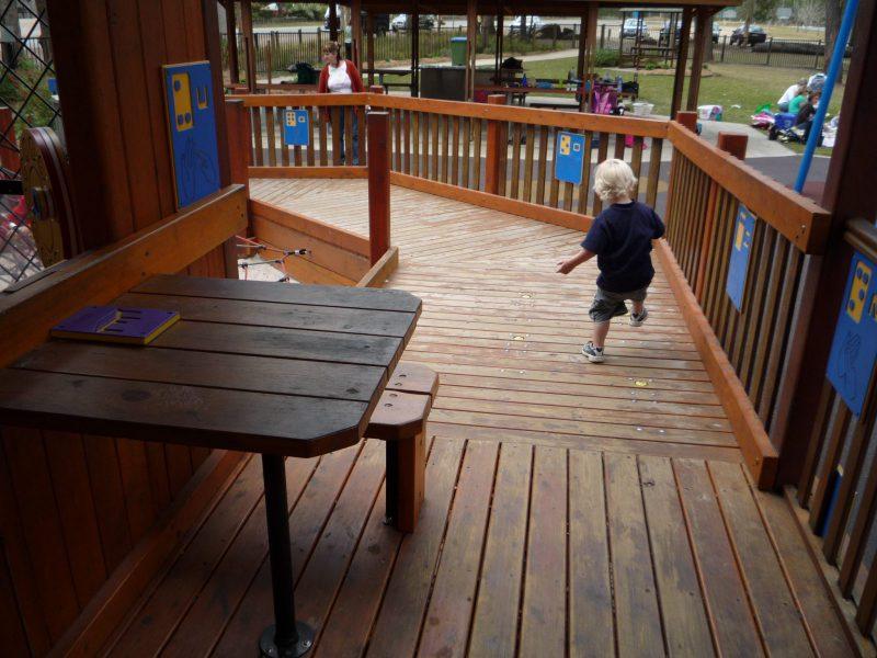 写真:幼い男の子がボタンを踏もうと懸命に足を上げているところ