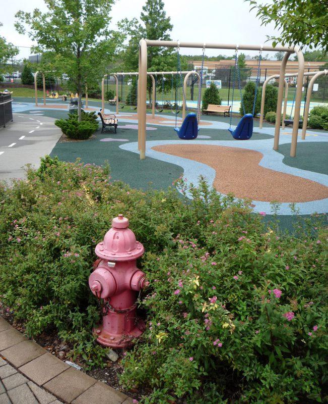 写真:広いブランコエリア。遊び場の地面は模様が描かれたゴムチップ舗装