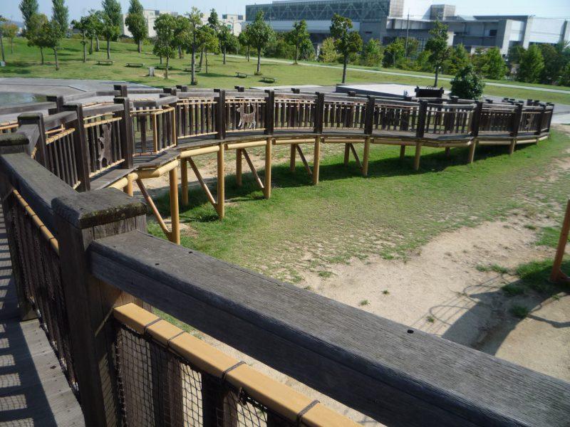 写真:巨大な複合遊具に付けられた長いスロープの例。所々に水平なデッキを挟み、カーブしながら約35メートル続く