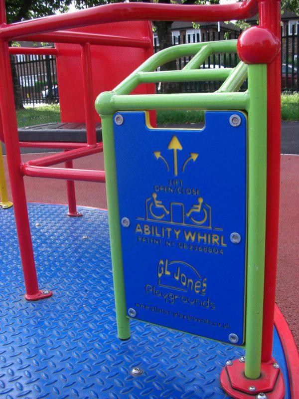 写真:鉄枠の付いた青いパネルに、車いすが向かい合わせで遊具に乗っている図と上向きの矢印が黄色で彫り込まれている