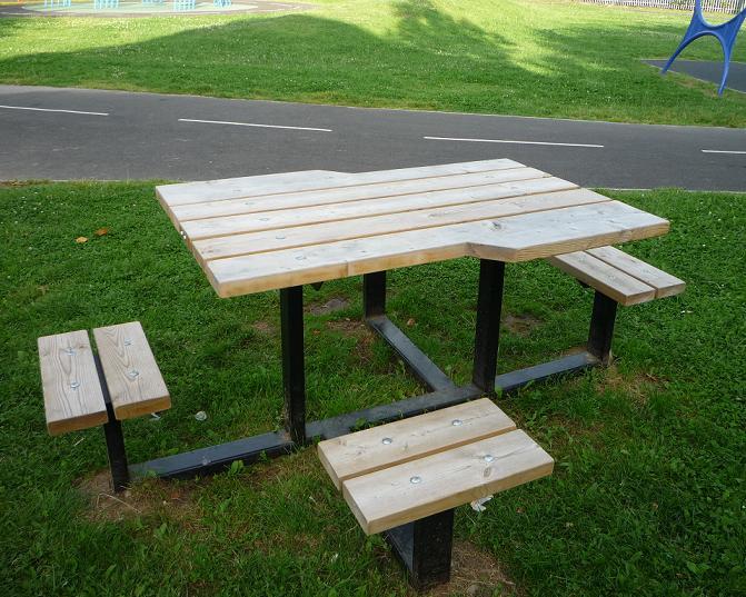 写真:芝地に置かれたピクニックテーブル。小さなベンチの隣に車いすの入れるスペース