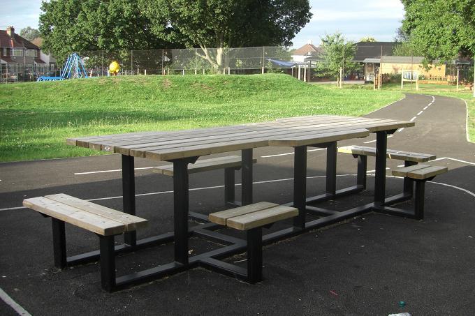 写真:ラウンドアバウトの中に置かれた大きなピクニックテーブル。車いすが2台並んだり、人が二人並んだり、いろいろな座り方ができる