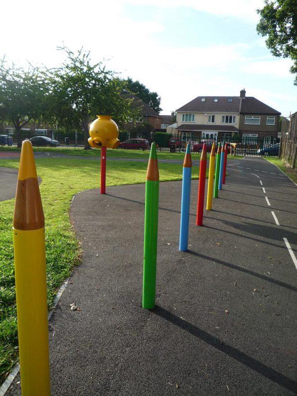 写真:園路の片側の縁に立ち並ぶ、高さ130センチほどの大きな色鉛筆の形をしたポール