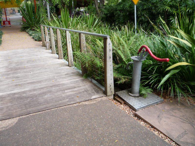 写真:橋のたもとにある手押しポンプ。蛇口は川のほうに向いている
