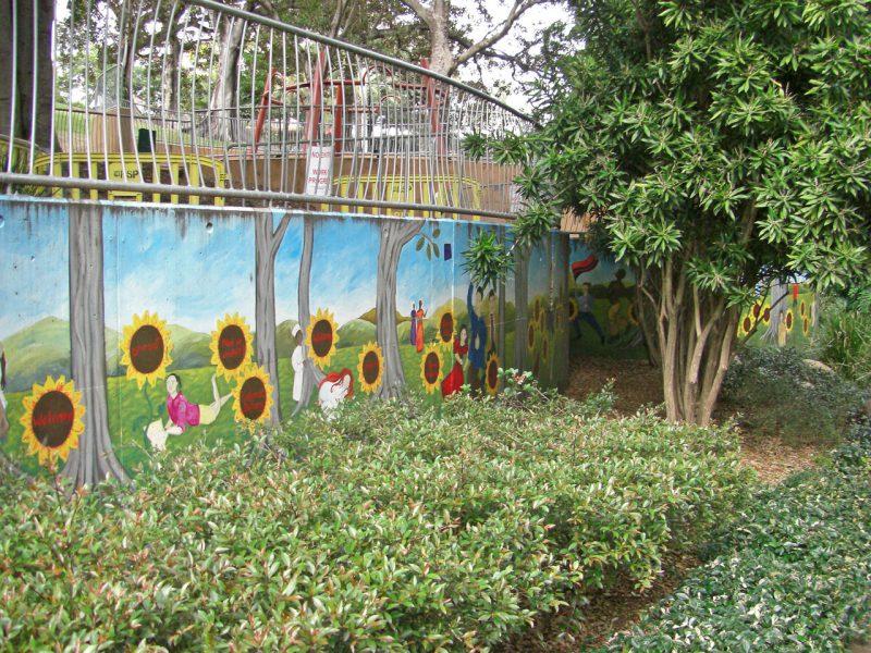 写真:長い壁に描かれた、周囲の緑の溶け込むような壁画