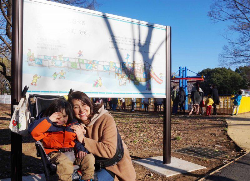 写真:「みんなのひろば」の看板の前で笑顔の龍円さんとニコくん