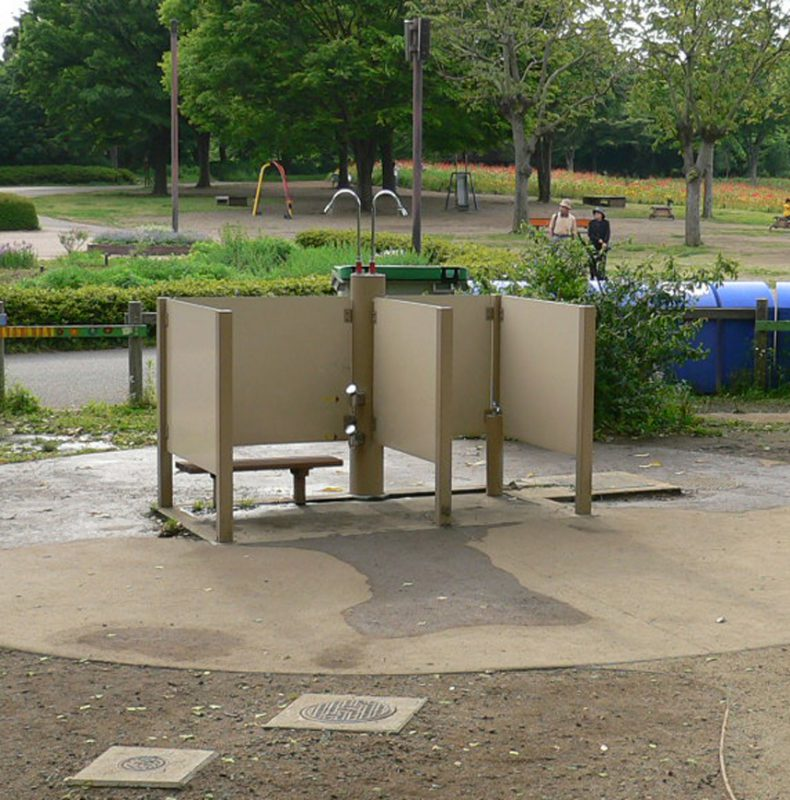 写真:2つのブースがあるシャワーコーナー。どちらも3面が部分的に覆われ、片方のブースはやや広くベンチもある