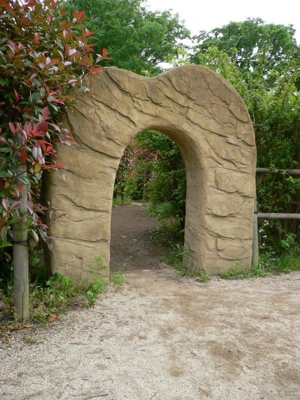 写真:生垣の間にあるゲート。その奥に小道が延びている