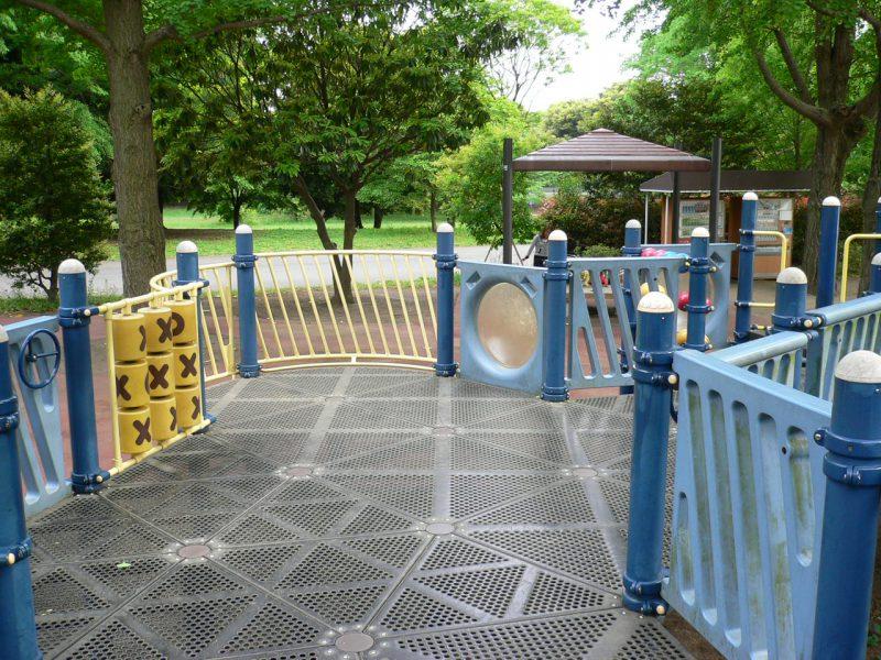 写真:複合遊具の広々としたデッキ。壁面に簡素なハンドル。また○と×が書かれた円柱状のパーツが縦横3つずつ並んだプレイパネル「チックタックトウ」。子どもの姿はない