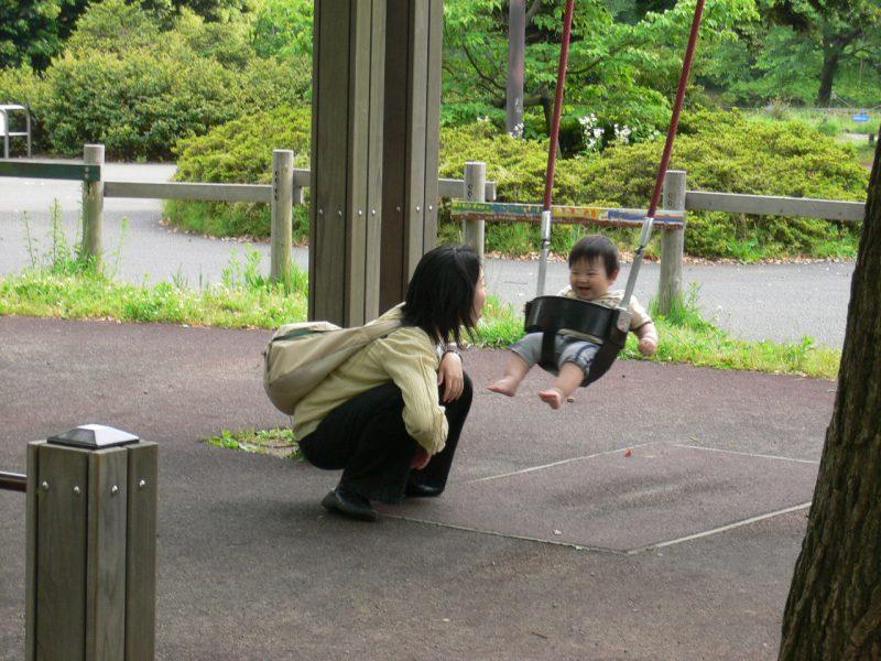 写真:幼児用のブランコに乗りご機嫌のあかちゃん。地面にしゃがんであかちゃんと笑顔を交わすお母さん