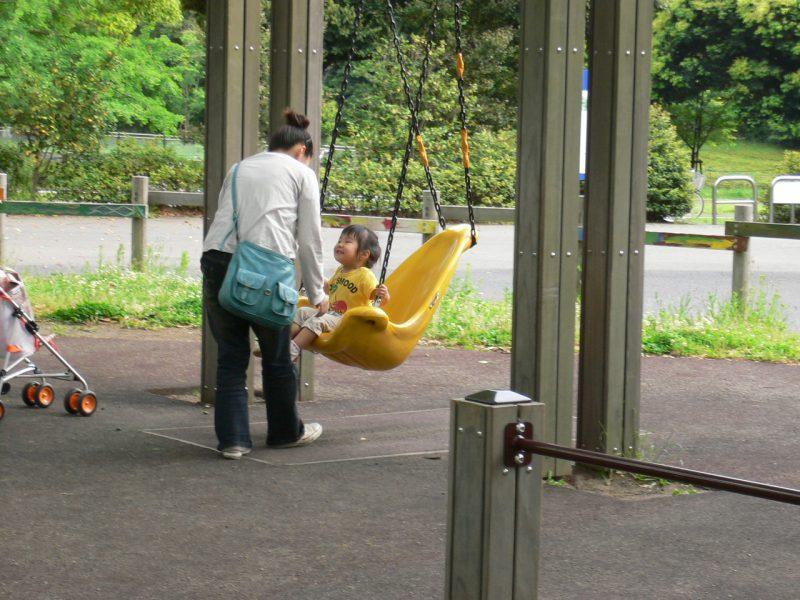 写真:背もたれ付きブランコに乗って笑顔になった小さな女の子。お母さんが正面に立ちブランコをそっと押す
