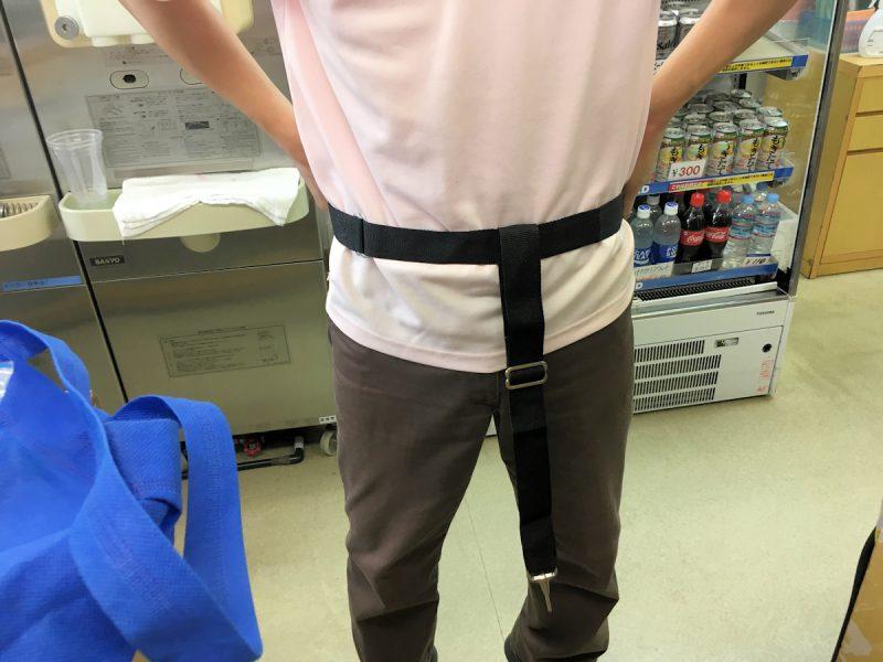 写真:売店の店員さん。T字のベルトを自分の腰に当てて説明中