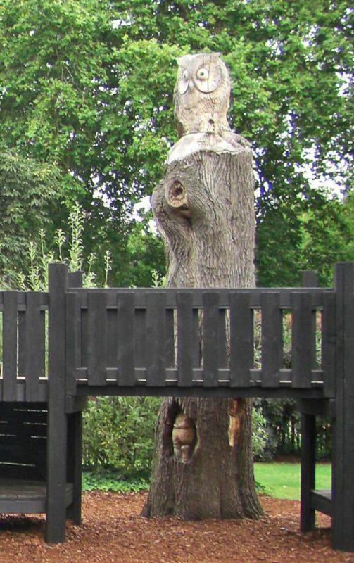 写真:木製複合遊具の隣に、昭和記念公園のものより一回り大きな木。やはり彫刻が施されている