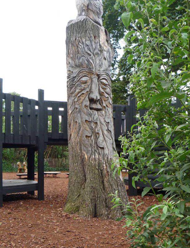 写真:幹の下の方には木のうろから覗く動物たち、中ほどの表面には木の精を思わせる大きな顔、てっぺんでは緻密に彫られた大きなフクロウが遊び場を見渡している