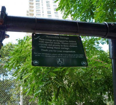 写真:梁と同じ深緑色の看板に、白い文字で書かれた文章。