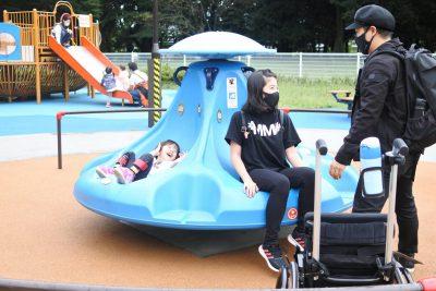 写真:回転遊具を回すお父さんと、笑顔のおねえちゃんと弟