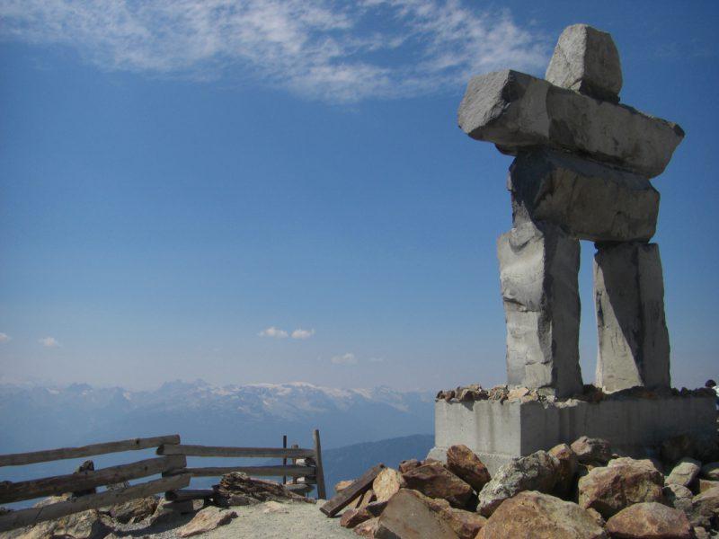写真:ウィスラー・マウンテンの山頂。オリンピックのエンブレムにもなった、巨大な石柱を人型に積み上げた像イヌクシュクが立っている。はるか遠くに雪の峰々が連なる