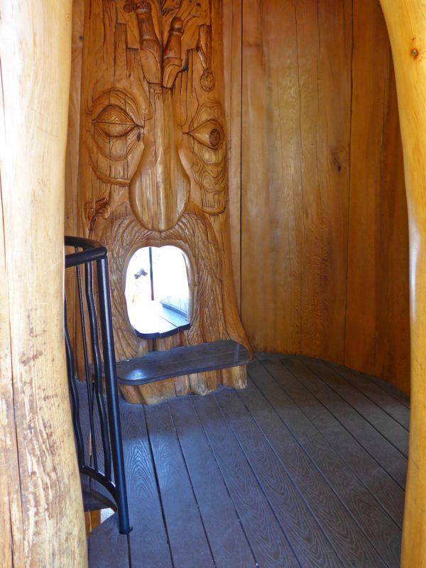 写真:中央の巨木の内側に空いた洞のような空間。広さは2畳ほど。内壁にはプリミティブな顔が大きく彫刻され、口の部分には穴が開いている
