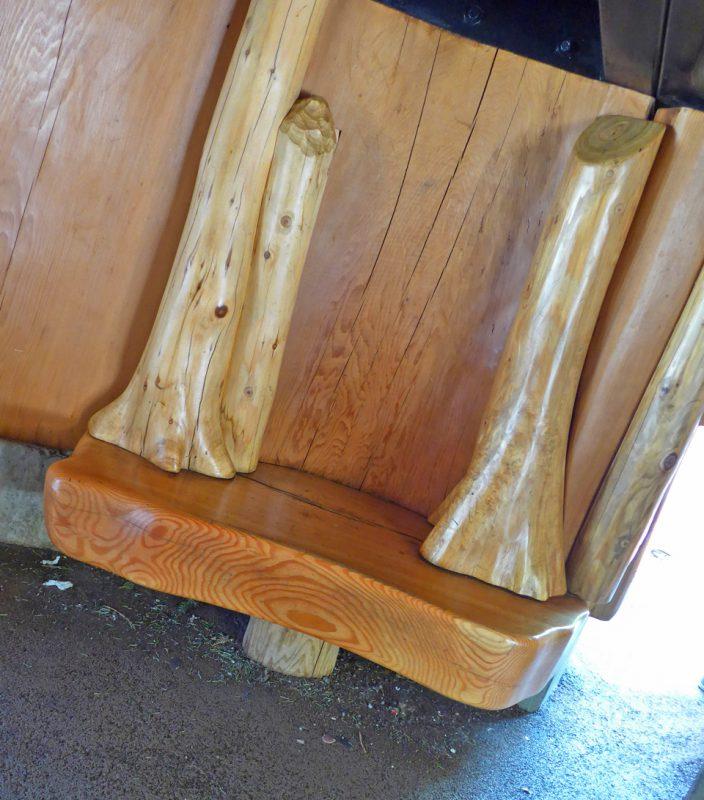 写真:中央の巨木の下の空間。壁際に小さな木のベンチ