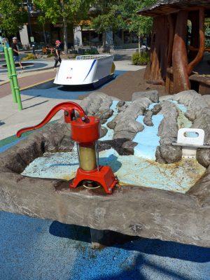 写真:上段の端に備え付けられた手押しポンプ。川の一つには板を上下させるタイプの簡単な堰がある