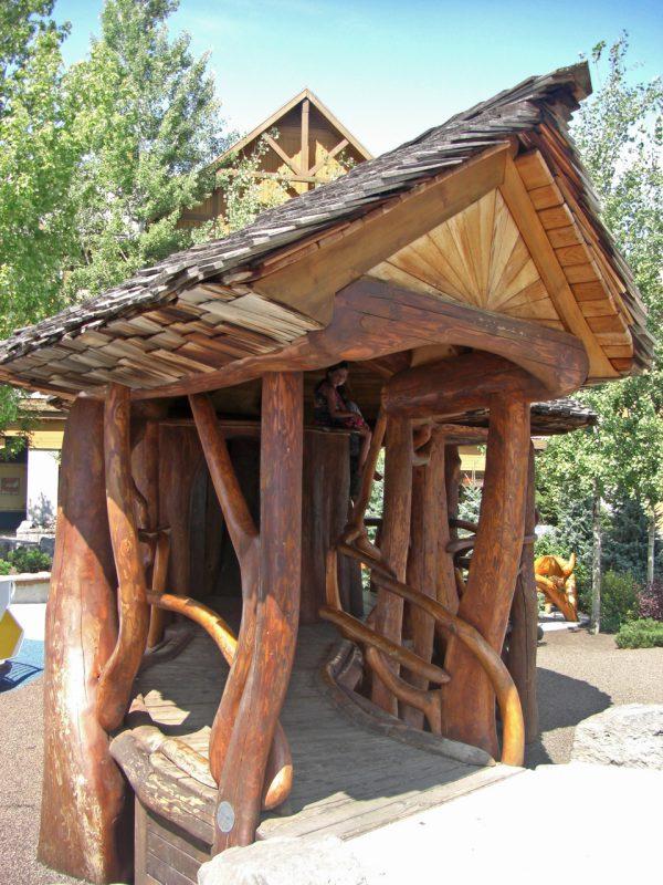 写真:カーブした渡り廊下のようなアプローチ。屋根は、板を少しずつずらして何重にも並べた素朴な風情の板葺き