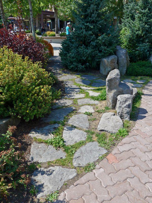 写真:園路の脇に延びる素朴な石畳の小路。両脇には色合いや表情が異なる多様な植物が配されている