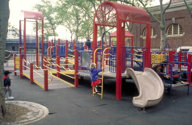 写真:公園の複合遊具。滑り台の隣には梯子があり、その向こうには折り返しのスロープがある。梯子を登り始めた女の子と、後ろから駆けて来る小さな男の子