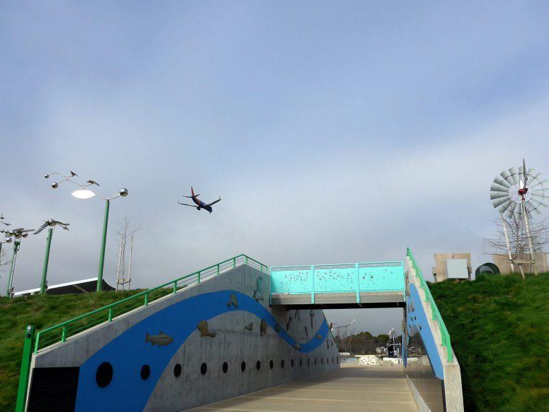 写真:土手の間を貫くアプローチ。上にはブリッジが架かり、空に飛行機の姿