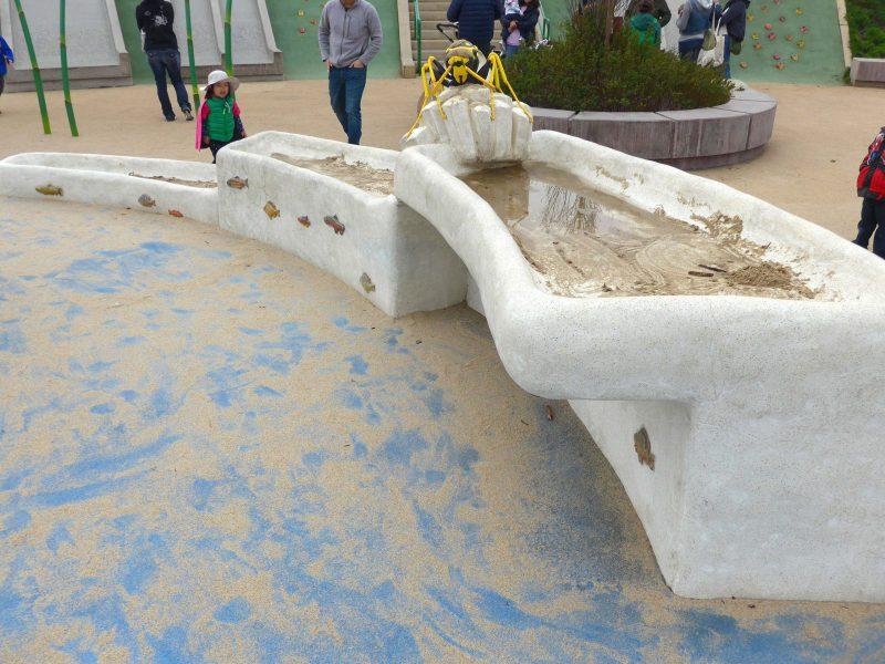 写真:モルタル製の砂遊びテーブル。砂はほとんど無く地面に散らばった状態