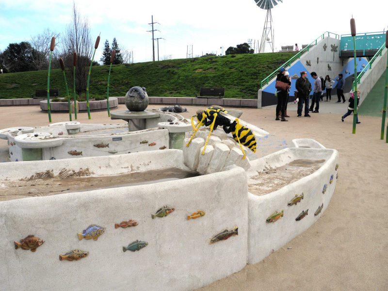 写真:砂場の縁に約60センチのリアルな蜂のオブジェ