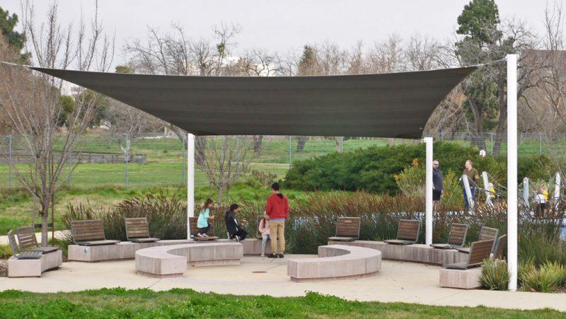 写真:石造りのベンチが丸く配置され、上には布製の日除け