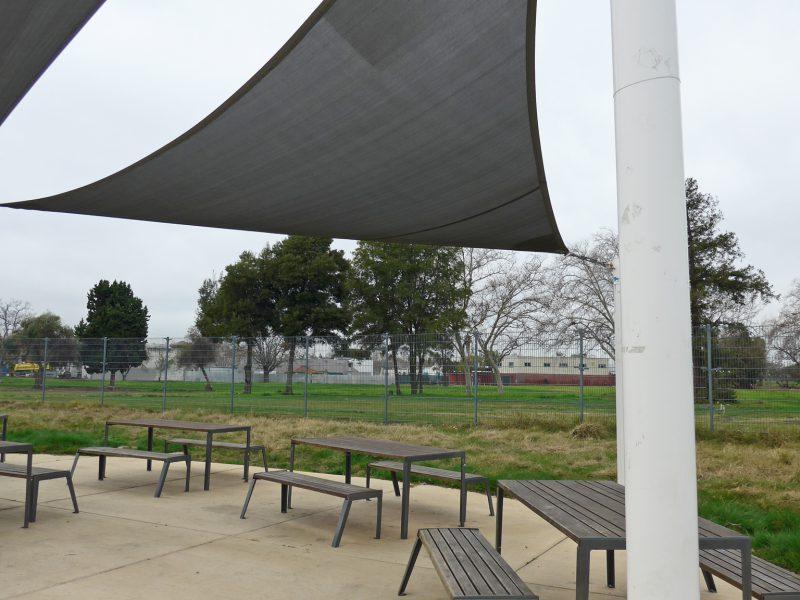 写真:テーブルと長椅子が並ぶピクニックエリア。上には日除け