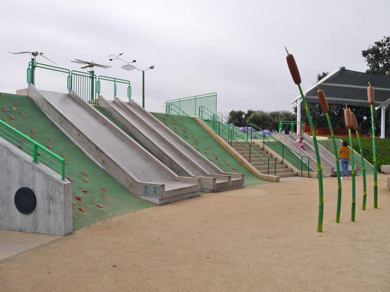 写真:土手の斜面に沿って並ぶいくつもの滑り台