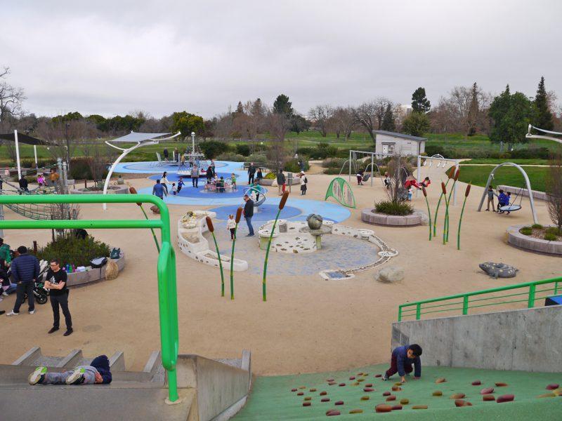 写真:大きな円形の遊び場のあちこちで親子連れが楽しんでいる