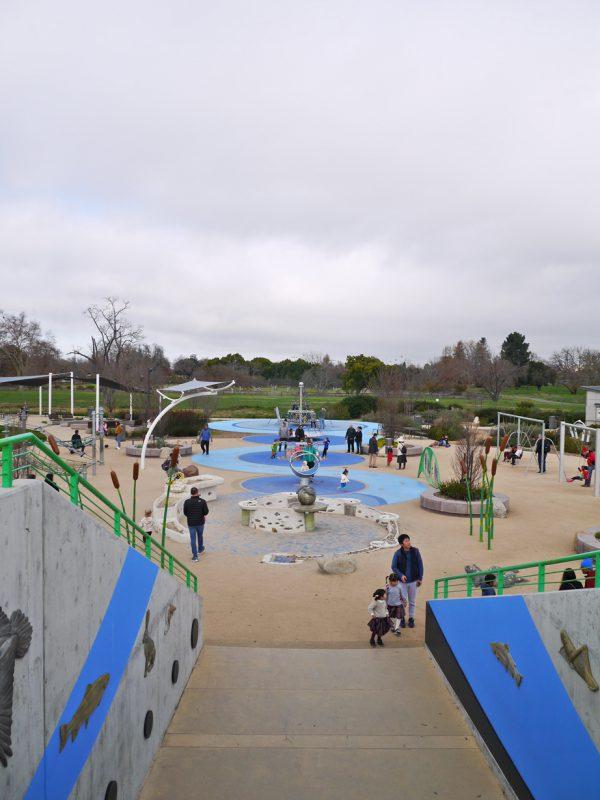 写真:遊び場を縦に貫くように並ぶ水や砂の遊び場、回転遊具、トランポリンなど