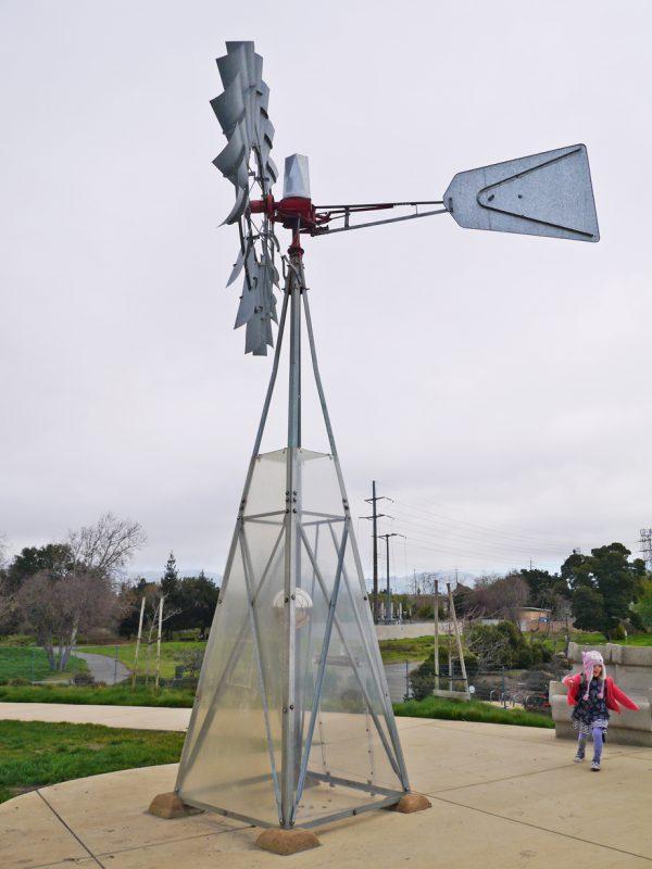 写真:4本の支柱を組んだ上に大きな風車。透明なパネルで囲われた支柱の真ん中に、直径30センチほどの球体がぶら下がっている