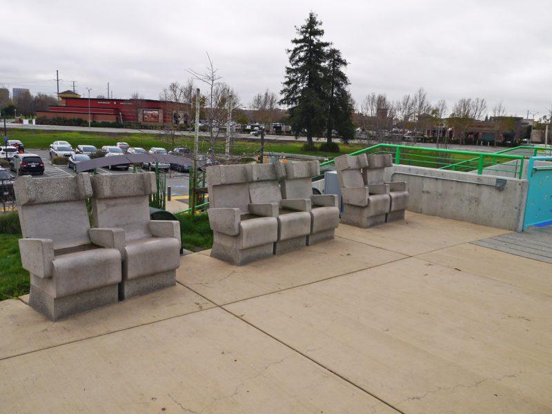 写真:遊び場を望む位置に、それぞれひじ掛け、背もたれ、ヘッドレストの付いた椅子が2席、3席、2席と一列に並んでいる