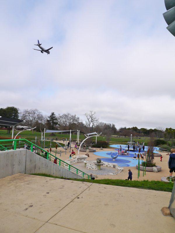 写真:轟音とともに現れた飛行機が、遊び場の手前から奥の方向で降下しながら飛んでいく。飛行機を見上げたり追いかけて走ったりする子どもたち