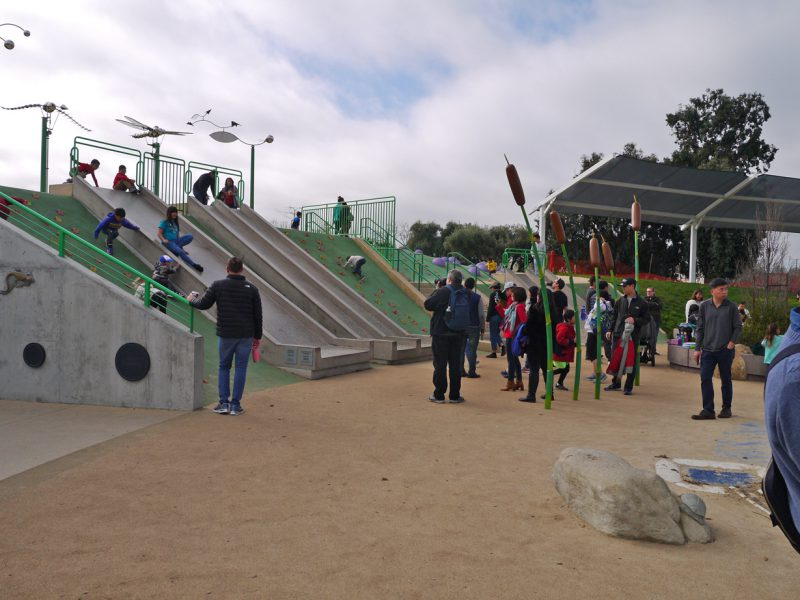 写真:滑り台を楽しむ子どもの年齢層は幅広い。下ではたくさんの親たちがおしゃべりをしながら見守っている