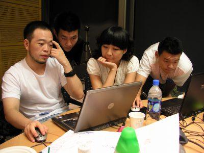 写真:若いデザイナーたちがパソコンを囲んでディスカッション