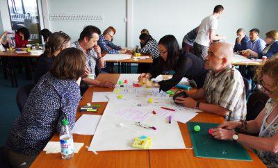 写真:海外でのワークショップの様子。各グループのテーブルにはカラフルなマジックやボール、カッターなどの小道具