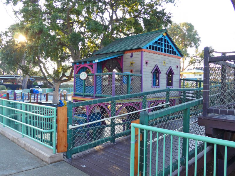 写真:星やハート型の小窓もあるプレイハウス。メインの遊び場は土地が一段低いため、今いる園路は建物の2階と同じレベル